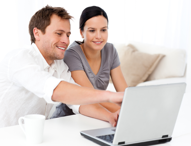 Cute man showing something on the laptop screen to his girlfriend in the living room