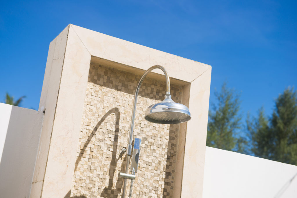 outdoor shower head with brick wall, clean