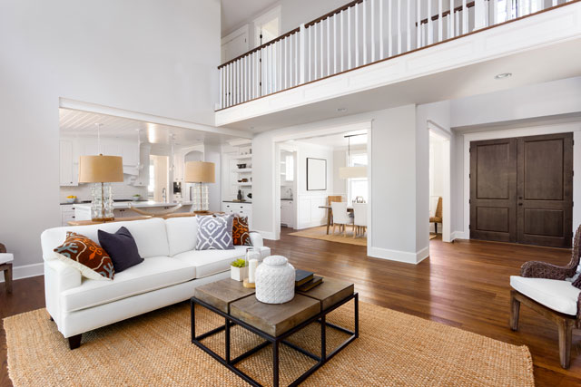 Beautiful, bright living room interior with high ceilings and second floor banister in new luxury home